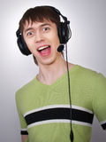 The joyful active boy in ear-phones sings Stock Photo