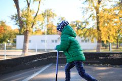 Joyful child is riding on a scooter along the street. Side view. A joyful and active child in a jacket and hat rides a scooter along the street in the autumn Royalty Free Stock Image