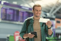 Joyful adult guy is holding boarding pass Stock Image