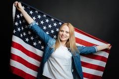 Joyful adult holding American flag in the studio royalty free stock photos