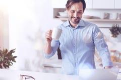 Joyful adult man using laptop in the kitchen Stock Image