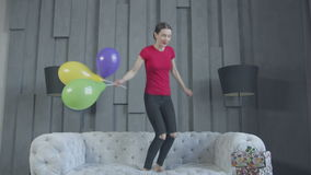 Excited birthday girl jumping on sofa at home. Joyful adult slim woman jumping on couch with colorful balloons in hand enjoying celebration of 30th anniversary stock footage