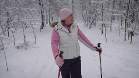 Joyful adult woman looking strangers. She stands in a snowy woods, around the trees grow tall. dressed in warm. Adult woman with appeasement look around. She stock video footage