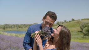 Loving couple bonding in blooming lavender field. Joyful affectionate african american man embracing , kissing charming beloved woman with bouquet of fragrant stock video footage