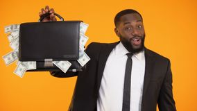 Joyful african-american businessman showing handbag with dollar cash, income. Stock footage stock video footage