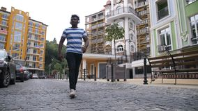 Joyful african american hipster dancing afrohouse. Joyful african american hipster man in trendy clothes walking down city street and dancing in afrobeat style stock video footage