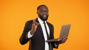 Joyful afro-american businessman holding laptop and showing ok sign, success. Stock footage stock footage