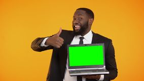 Joyful afro-american businessman showing prekeyed laptop and thumbs-up gesture. Stock footage stock footage