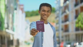 Joyful afro-american male teen showing passport and smiling on cam, citizenship. Stock footage stock video