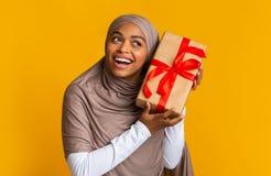 Joyful afro muslim woman in headscarf holding gift box near ear