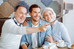 Joyful aged couple and their grandson resting in the cafe. Enjoy the moment. Pleasant loving aged couple and their grandson sitting in the cafe and making Royalty Free Stock Photos