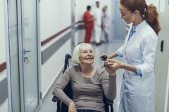 Cheerful lady on pushchair is talking to female doctor stock images