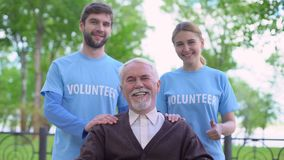 Joyful aged pensioner and two volunteers showing thumbs up, social support fund