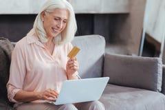Joyful aged woman enjoying online shopping Royalty Free Stock Photo
