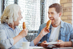 Joyful aged woman and grandson eating patties in the cafe. Home made baking. Pleasant caring aged women and her grandson eating patties and sresting in the cafe Royalty Free Stock Image