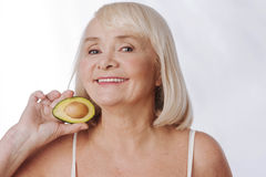Joyful aged woman holding half of an avocado. Doze of vitamins. Joyful positive aged woman standing against the white background and smiling while holding half royalty free stock photo