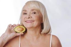 Joyful aged woman holding half of an avocado Royalty Free Stock Photo