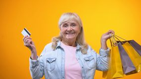 Joyful aged woman showing shopping bags and bank card, services for retirees. Stock footage stock footage