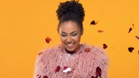 Joyful american woman standing under falling heart-shaped confetti, valentine