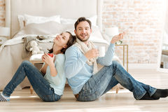 Joyful amused couple drinking hot tea in the bedroom Royalty Free Stock Photos