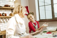 Joyful amused young light-haired girl inspecting condition of cookies stock images
