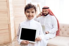 Joyful Arab boy looks at computer tablet while father works. stock photos