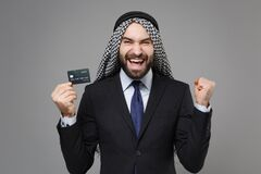 Joyful arabian muslim businessman in keffiyeh kafiya ring igal agal classic suit isolated on gray background