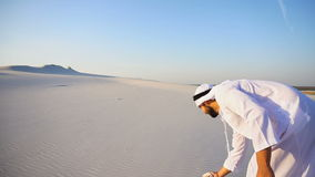 Joyful Arabian Sheikh man walks on top of desert with smile on face on clear summer day outdoors. Charming young male Arab looks toward sun and goes up sand stock video footage