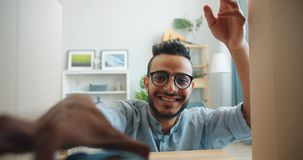 Joyful Arabian student opening box getting present smiling at home. Joyful Arabian student handsome guy in glasses is opening box getting present smiling at home stock footage