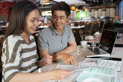 Studying Details of Life Insurance Policy. Joyful Asian couple in casualwear sitting at table of spacious cafe and studying details of life insurance policy Royalty Free Stock Photography