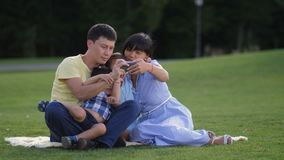 Joyful asian family with kids taking selfie in park stock video footage