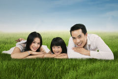 Joyful asian family lying on grass. Portrait of happy asian family lying on grass and smiling at camera Royalty Free Stock Images