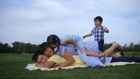 Joyful asian family piled on top of dad in park. Excited smiling asian family with cute siblings piled on top of happy father in summer park. Beautiful multi stock footage