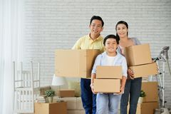 Joyful Family Moving in New Apartment. Joyful Asian family of three holding moving boxes in hands and looking at camera with toothy smiles while relocating to stock image