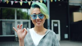 Joyful Asian hipster girl showing OK gesture smiling outside in city street. Slow motion portrait of joyful Asian hipster girl showing OK gesture smiling outside stock footage
