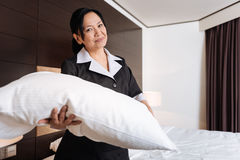 Joyful Asian hotel maid standing in the hotel room. Hotel room. Joyful good looking hotel maid standing in the hotel room and smiling while changing the bedding Stock Photo