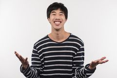 Joyful Asian man expressing his emotions. Excellent mood. Joyful Asian man smiling while expressing his positive emotions Stock Image