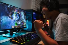 Joyful asian teen gamer man playing video games on computer in d. Ark room wearing headphones and using backlit colorful keyboard stock photography