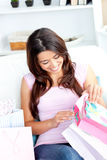 Joyful asian woman with shopping bags on the sofa Stock Image