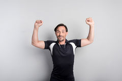 Joyful athletic man showing his muscles Stock Photos