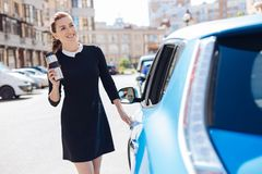 Joyful attractive businesswoman smiling. Positive mood. Joyful attractive smart businesswoman opening her car and smiling while having a thermo cup in her hands Stock Photography