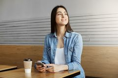 Joyful attractive girl with dark hair sitting in cafe, drinks coffee and chatting with friend on smartphone then turning Royalty Free Stock Images