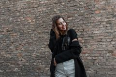 Joyful attractive young woman with a cute smile in a stylish coat in a black T-shirt in fashionable white jeans poses. In the city near a vintage brick wall stock photo