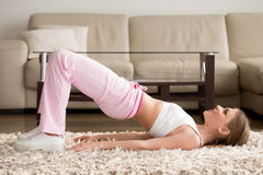Woman in sportswear doing hip bridge exercise. Joyful attractive young woman lying on floor in living room and doing hip bridge exercise. Happy smiling lady in Royalty Free Stock Images