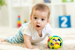 Joyful baby crawling on the floor in nursery room stock images