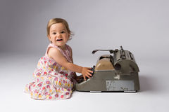 Joyful Baby Girl and Her Toy. Cute joyful baby girl having fun with an antique typewriter Royalty Free Stock Photography