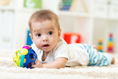 Joyful baby lying on the carpet in nursery room royalty free stock photos