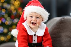 Joyful baby wearing santa disguise in christmas. Joyful baby wearing a red santa clays disguise on a couch at home in christmas with a tree in the background royalty free stock image