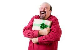 Joyful balding man holding present to chest Stock Image