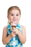 Joyful barnflicka som äter glass i den isolerade studion Arkivbilder